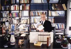 A.C dans son bureau. Entouré de quelques-unes de ses principales traductions, l'Univers de la Bible, la Bible ; A. Chouraqui tient dans ses mains, son autobiographie, L'Amour fort comme la mort.